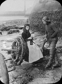 ca. 19th century --- A woman sits knitting on a beach whilst a man in large boots and a fisherman's hat stands beside her.