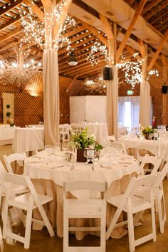 Chic white chairs and simplecenterpieces #wedding #tablescape