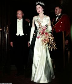 1952: The Queen in a Norman Hartnell black and white satin magpie dress for a royal premiere at Leicester Square. The dress was copied and was in the shops within 24 hours