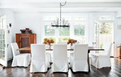 Genial White Slipcovered Henriksdal Chairs From Ikea Surround An Antique Table In  The Airy Dining Room.