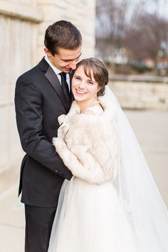 David's Bridal bride Jaclyn layered a faux fur wrap over her tulle A-line wedding gown with cap sleeves for her traditional winter wedding.