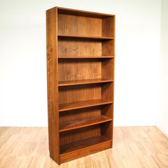 This tall danish modern bookcase is featured in a solid wood with a gorgeous glossy teak finish. This bookshelf features a sleek and modern design with 5 shelf tiers and adjustable heights. Perfect for displaying books and knick knacks! #danishmodern #storage #bookcase&shelving #sandiegovintage #vintagefurniture