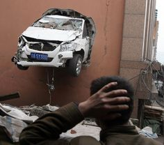 A driver smashed through the wall of a second floor car park in Chongqing, China, after mistaking the accelerator for the brake. The vehicle was then left poking precariously out the side of the structure. Huang Xiaoping, who lives next to the car park, saw the incident. He said: 'I heard two explosion sounds. When I came out I saw a car was stuck on the wall on the second floor of the car park building, and the front wheels were still rotating. I thought it was a movie shoot.'