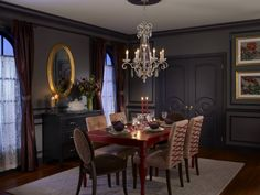 This gorgeous dining room has dark eggshell walls, rich gray trim, flowing lace curtains and a bold gilded mirror. A crystal chandelier glistens above a table set with with traditional flatware and mismatched chairs. Grey Dining Room Paint, Best Dining Room Colors, Grey Room, Dining Room Design, Dining Rooms, Dining Area, Paint Sheen, Gloss Paint, Interior Design 2017