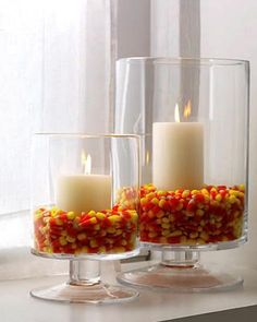 Fill hurricanes one third full with candy corn and nestle white pillar candles inside.