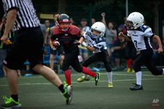 In this Sunday, July 2015 photo, a young player dodges a pair of opposing tacklers during their American football game in Beijing. The Allure, American Football, Beijing, Football Helmets, Sunday, Pairs, Digital, World, Simple