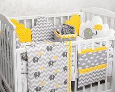 kit berço amarelo com estampas diversas e elefantinho na cabeceira