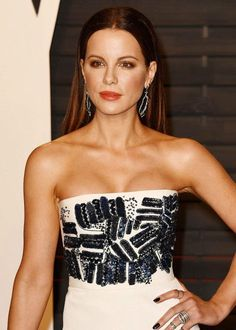 Kate Beckinsale looked gorgeous and dazzling in a pristine strapless white gown with embroidered bodice and hour glass shape, which accentuated her gorgeous figure, while posing for the photographs on the red carpet at the 2016 Vanity Fair Oscar Party held at the Wallis Annenberg Center for the Performing Arts on February 28, 2016 in Beverly Hills, California.