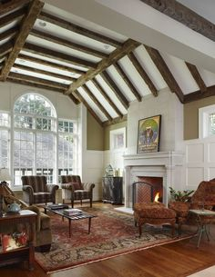 Traditionally ornate living room, including wood frame chairs and sofa, patterned area rug on hardwood flooring, and white stone fireplace, stand beneath white ceiling with natural wood exposed beams.