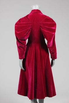 Elsa Schiaparelli couture deep fuchsia velvet evening coat, late 1930s, bearing printed petersham Paris label and numbered 91184, the front bodice with curved multi-darted seams which sweep down to form a curve at the narrow rear waist, with dramatic fan-shaped pleats forming leg o' mutton sleeves, four large celluloid disc buttons inset with glitter and beads, high stand angular collar, silk lining