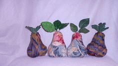 """This is a listing for 4 soft fabric pears-about 5.5"""" tall by 5"""" wide at their bases..  They are all made from recycled/upcycled materials.  Two of them are home decor remnants with  a floral design in shades of green,gold and pink/red on dark tan/khaki. The other two are fabric scraps with a very cool paint splatter effect in shades of blue, black and red on brown.  They are topped with polyester leaves scavenged from old floral arrangements.  The center of each leaf set has a pearl…"""