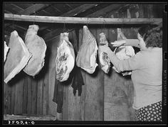 Wife of tenant farmer cutting piece of ham in smokehouse near Pace, Mississippi. Background photo for Sunflower Plantation (1939 Jan)
