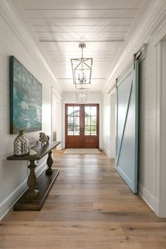 This gorgeous foyer feature shiplap walls, tongue and groove paneling ceiling and blue barn door painted in Benjamin Moore Yarmouth Blue.