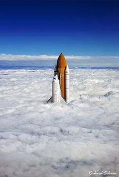 A space shuttle emerges from the clouds.