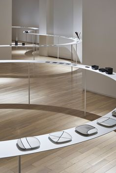 Cups, plates and cutlery are lined up in single file on this table, which snakes through the various rooms of a gallery at Nendo's Colourful Shadows exhibition.