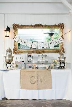 coffee bar with a hanging banner, burlap detail, and pastel florals, created by Cedarwood Weddings.