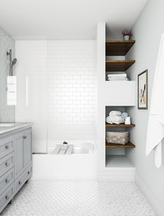 Go for the classic, all-white bathroom. The look stays interesting with complementary mosaic and subway tile shapes. A touch of light gray at the vanity and dark brown shelves balance the look, but…More White Bathroom Tiles, Bathroom Tile Designs, Grey Bathrooms, White Tiles, Bathroom Interior Design, Bathroom Flooring, Modern Bathroom, Shower Bathroom, Bathroom Ideas