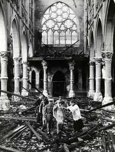 Catholic priest Father Finn assists British Army Fusilier Tom Dowling and his new bride Miss Martha Coogan through the rubble of a destroyed London Catholic church in which they were just wed. September 14, 1940.