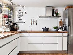 Cocina con muebles blancos, encimera de madera y electrodomésticos de acero