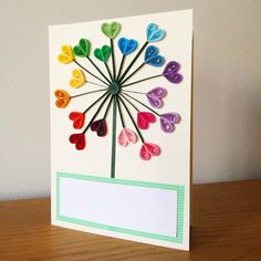 Blank greeting card with quilled heart dandelion decoration. The card is decorated with 18 hand quilled hearts, a technique by which paper is carefully curled and glued to create beautiful paper art. The flowers are then arranged and glued in a dandelion shape, with space for a customised