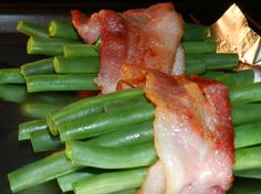 Brown Sugar & Bacon Wrapped Green Beans Makes 6 bundles  1 pound fresh green beans  6 strips of bacon  3 Tbls butter  1 clove garlic, minced  1/4 C. brown sugar  Preheat oven to 400 degrees. Boil green beans until slightly tender. Meanwhile fry bacon until about 3/4 cooked keeping it soft. Degrease bacon on a paper towel and drain beans. Slice bacon strips in half. Wrap the bacon around several beans & lay on baking sheet. Bake 10 minutes  Heat butter, garlic & brown sugar pour on beans
