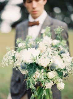 Garden bouquet:  Fluffy white blooms, a touch of blue thistle, and freeform greenery form the most beautiful and lush arrangement