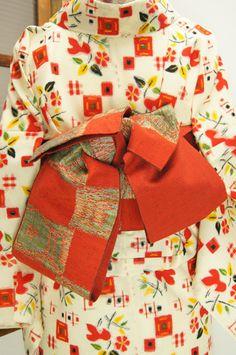 どこか愁いをおびたしっとりと落ち着いた朱色とグレーのバイカラーを基調に織り出された、梅鉢亀甲、遠州椿亀甲の飾り模様が味わい深い大きな市松模様がレトロモダンな半幅帯です。