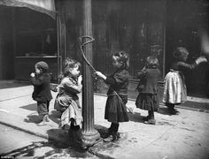 ERA VICTORIAN: photographer unknown - making their own fun, children skip and play around a lamp post. The little boy has bare feet while the rest of children wear shoes. Little girl with back turned has quite ragged clothing on. These were VERY tough times for poor families. http://www.victorian-era.org/victorian-poor-and-middle-class.html       ~~pεαςε and l๏vḕ <3