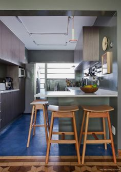 Cozinha integrada com parede cinza e piso de ladrilho hidráulico azul.