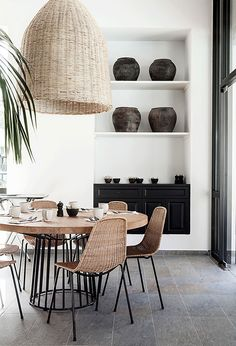 Great dining area with a round dining table, woven chairs and a woven pendant light. We love the black details and the great atmosphere in this room! Check out our website to find more inspiration!