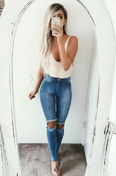 Cream tank, waistlength platinum blonde hair, tan skin, distressed blue denims
