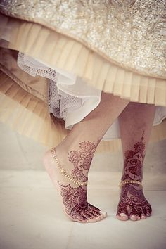 lovely henna on the feet under this multi-textured, weighted, and layered skirt