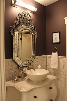 A small powder room beautifully decorated with a Venetian glass mirror.