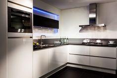 Een compacte greeploze hoekkeuken (formaat 315 x 232 cm) in de kleur hoogglans wit. Als contrast zijn de klepkasten aan de wand uitgevoerd in de kleur eiken terra. Naast de keuken is hier ook de combi-magnetron in greeploos uitgevoerd.