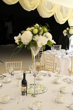 Martini vases filled with lemon roses, white freesia, white phalaeonopsis orchids, white hydrangea white oriental lilies and complimentary foliages made up these table centrepieces for a lovely country marquee wedding.