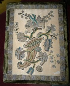 It is a 19thc bible (or book) box from the Victorian era. I am uncertain of origin but must be French or Italian. Featuring an exotic floral in the Jacobean fashion embroidered onto a cream silk ground. The thick embroidery is has metallic throughout. The emerald green silk velvet is in excellent condition as is the metallic galon trimming around the edges of the box