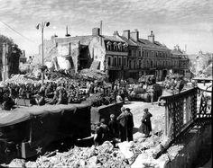 Troupes US parmi des civils, chars Sherman, véhicules: camion GMC et Jeep Place Gambetta (aujourd'hui Place général de Gaulle) à Isigny sur Mer en ruines.