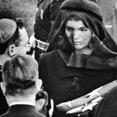 PhotographDescriptionJacqueline Kennedy at President John Kennedy's funeral. She receives the comfort of a priest after accepting the folded American flag that covered her late husband's coffin. Jacqueline Kennedy Onassis, John Kennedy, Estilo Jackie Kennedy, Les Kennedy, Jaqueline Kennedy, Carolyn Bessette Kennedy, John John, Jfk Funeral, Familia Kennedy