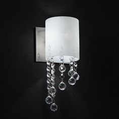 Crystal bead droplets shimmer against chrome hardware on this one light wall sconce, diffusing the light from the warm matte opal shade. This classic style sconce is the perfect accent for any modern lighting design.