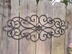 Like the idea of hanging some wrought iron stuff on the backyard fence. It would go with the bench (and with the swing I hope to get).