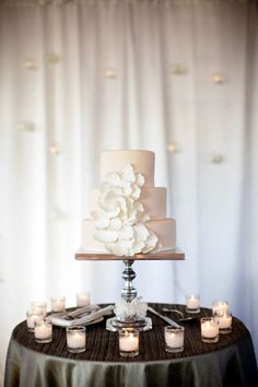 Mesa de bolo de casamento simples, perfeita para casamento ao pôr-do-sol: velas ao redor da mesa iluminam o bolo discretamente