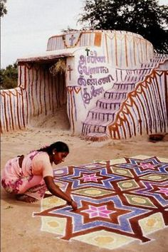 illuminatetheworld:    A woman painting a kolam in Tamil Nadu, India. A kolam is a form of sandpainting that is drawn using rice powder by female members of the family in front of their home.