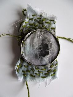 image transfer on dyed, frayed, muslin sticthed to a hand formed aluminium frame.  Use of scraps, stitch  and photos!  Bezel construction. Metal and stiff fabric Tape measures. Stitched to join.    Collaboration Inspiration  AlysPower with Ruth Singer