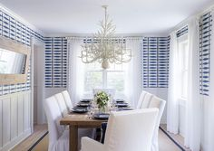 East Hampton Beach Cottage - Beautiful coastal Dining Room features bleached wood floors, sisal rug, slipcovered white cotton chairs, blue and white wallpaper and white sheer drapery.