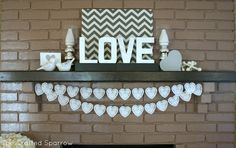 """I """"LOVE"""" this mantel! The letters to spell """"love"""" are just paper mache spray painted metallic silver and the heart bunting is made out of inexpensive paper doilies."""