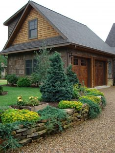 #HomeOwnerBuff wooden home garage. I love this garage door and landscape with the stone.