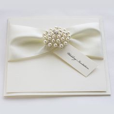 Satin Pearl wedding invitations with luxury satin ribbons and a crystal cluster embellishment.