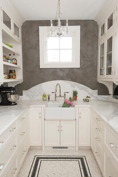 A Mini George II Chandelier illuminates a farmhouse sink and nickel deck-mount faucet finished with a white curved marble backsplash tucked under a window.