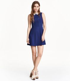 Sleeveless dress in woven crêpe fabric with a lace collar. Decorative pin-tucks at front, concealed zip at back, seam at waist, and gently flared circle skirt. Unlined.