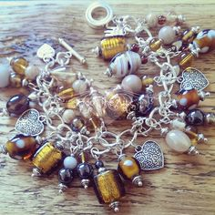 Gorgeous golden browns in this unique handmade charm bracelet. Luxury Indian glass beads and Tibetan style silver heart charms #charm #bracelet #brown #glass #beads #silver #handmade #madeinuk #jewellery #fashion #accessories #pretty #unique #fashion #handmade #madetoorder #chic #fromtheattic